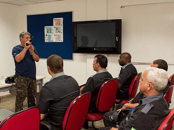 Nossa Historia - Grupo de vigilantes em sala de aula recebendo instrução.