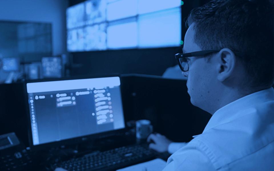 CFTV e Alarmes - Foto de uma central interna de monitoramento de Alarmes com um agente de vigilância navegando em uma tela do painel de controle interno.