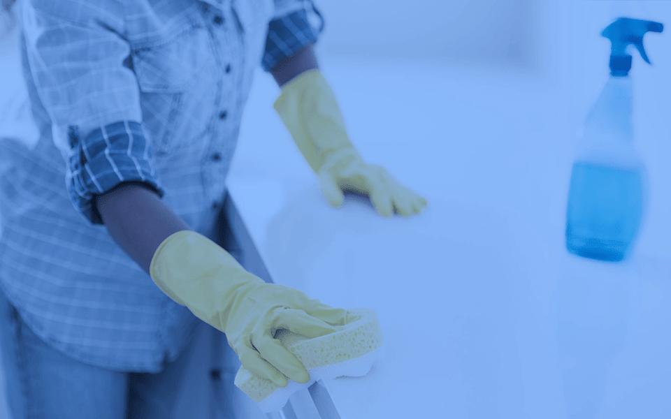 Facilities Macor - Imagem de agente de limpeza segurando uma esponja sobre um balcão.