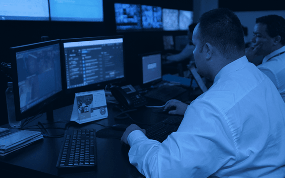 Monitoramento de Alarmes - imagem de agente de monitoria sistema interno de frente para duas telas.