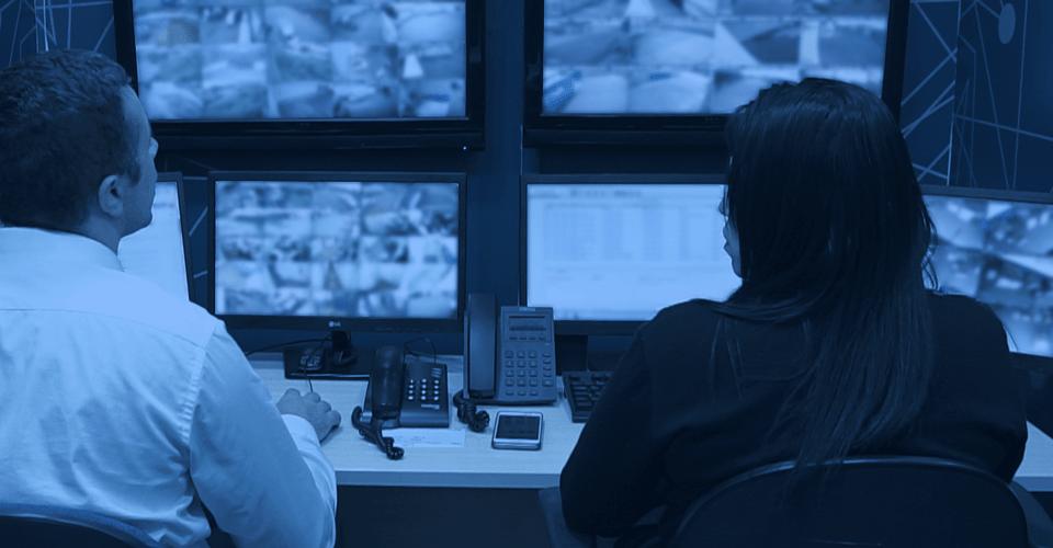 Monitoramento de Alarmes - Foto de uma central interna de monitoramento de Alarmes com dois agentes de vigilância observando 4 telas, de costas.
