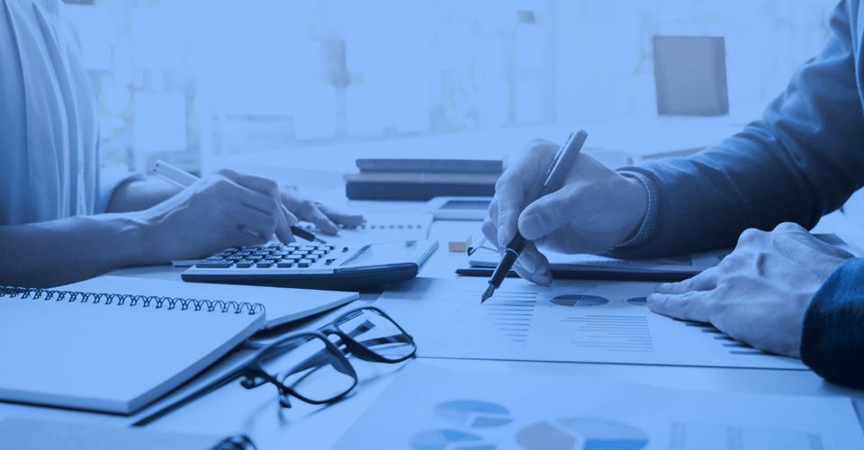 Orçamento - imagem de uma mesa, com documentos e papéis espalhados, de um lado um homem segura uma caneta, e do outro uma mulher usa uma calculadora.
