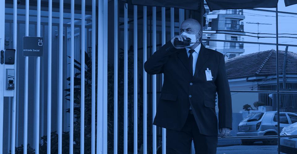 Segurança Patrimonial- imagem de um segurança utilizando um rádio transmissor em frente a uma portaria.